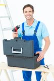 Happy carpenter removing drill machine from tool box. Portrait of happy carpenter removing drill machine from tool box over white background royalty free stock image