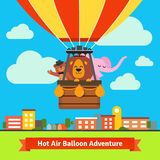 Happy cartoon animals flying on hot air balloon Stock Image