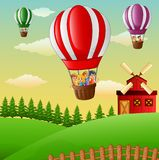 Happy cartoon kids flying in a hot air balloon in the farm Stock Photo