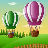 Happy cartoon kids flying in a hot air balloon Stock Photography