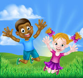 Happy Cartoon Kids Jumping. Happy cartoon young boy and girl, one black and one white, jumping for joy outdoors in a field Royalty Free Stock Photography