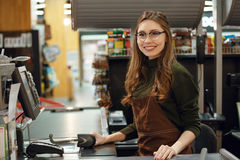 Happy cashier woman on workspace in supermarket shop. Image of happy cashier woman on workspace in supermarket shop. Looking aside Royalty Free Stock Images