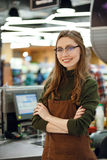Happy cashier woman on workspace in supermarket shop. Image of happy cashier woman on workspace in supermarket shop. Looking at camera Royalty Free Stock Photo