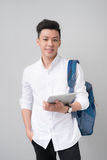 Happy casual asian male student using tablet computer isolated o. N a gray background Stock Images