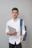Happy casual asian male student using tablet computer isolated o Royalty Free Stock Photos