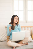 Happy casual beautiful asian young woman working on a laptop at Royalty Free Stock Photo