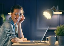 Woman working on a laptop. Happy casual beautiful woman working on a laptop at the night at home Stock Photo