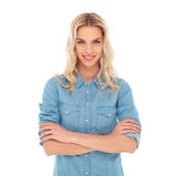 Happy casual blonde woman standing with hands crossed Stock Photo