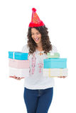 Happy casual brunette with party hat holding presents Stock Photography