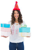 Happy casual brunette wearing party hat holding presents Royalty Free Stock Photo