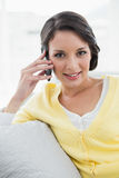 Happy casual brunette in yellow cardigan calling with her mobile phone Royalty Free Stock Photo