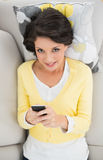 Happy casual brunette in yellow cardigan using a mobile phone Stock Photos