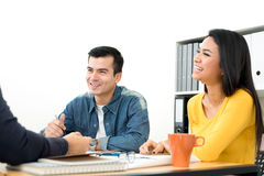 Happy casual business people laughing and smiling in the meeting stock photo