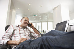 Happy Casual Businessman With Feet On Desk Using Phone Stock Images