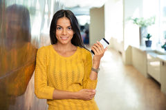 Happy casual businesswoman holding smartphone Stock Photos