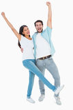 Happy casual couple cheering together Stock Photo