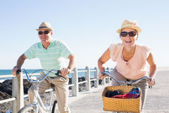 Happy casual couple going for a bike ride on the pier Stock Images
