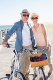 Happy casual couple going for a bike ride on the pier Royalty Free Stock Image