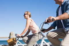 Happy casual couple going for a bike ride on the pier Royalty Free Stock Photos