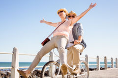 Happy casual couple going for a bike ride on the pier Stock Photo