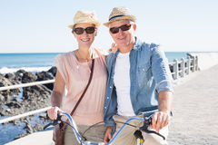 Happy casual couple going for a bike ride on the pier Stock Photos