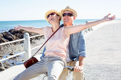 Happy casual couple going for a bike ride on the pier Royalty Free Stock Photography