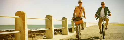 Happy casual couple going for a bike ride on the pier Royalty Free Stock Images