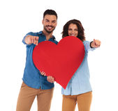 Happy casual couple holding big heart and pointing fingers Royalty Free Stock Photos