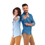 Happy casual couple pointing fingers. Back to back casual couple pointing fingers to the camera on white background Stock Photos