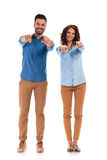 Happy casual couple pointing their fingers Stock Images