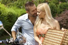 Happy casual couple with scooter and picnic basket. Happy casual caucasian couple with scooter and picnic basket. Blonde smiling women with handsome man, outdoor Stock Photo