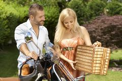 Happy casual couple with scooter and picnic basket Stock Images