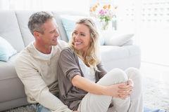 Happy casual couple sitting on rug Stock Photo