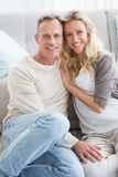 Happy casual couple sitting on rug smiling at camera Royalty Free Stock Photos