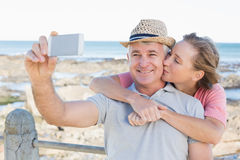 Happy casual couple taking a selfie by the coast Stock Photo