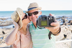 Happy casual couple taking a selfie by the coast Stock Images