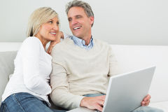 Happy casual couple using laptop in at home Stock Photo