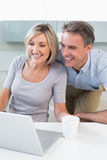 Happy casual couple using laptop in kitchen Stock Photos