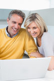 Happy casual couple using laptop in kitchen Royalty Free Stock Images