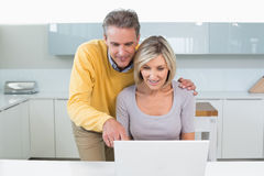 Happy casual couple using laptop in kitchen Stock Images