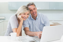 Happy casual couple using laptop in kitchen Royalty Free Stock Photography