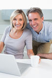 Happy casual couple using laptop in kitchen Royalty Free Stock Photos