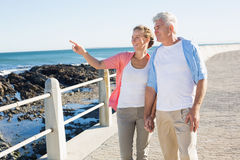 Happy casual couple walking by the coast Royalty Free Stock Photo