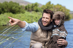 Happy casual father and son at a lake. In the countryside Royalty Free Stock Image