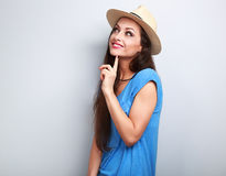 Happy casual fun woman in summer hat and blue top thinking and l Stock Images