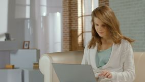 Happy casual girl busy, working on project using laptop at home. Stock footage stock footage
