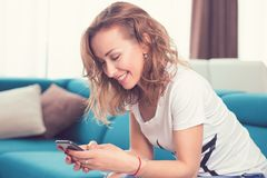 Happy girl texting on a mobile phone resting on a couch at home Royalty Free Stock Photo