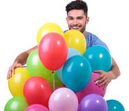 Happy casual man embracing a bunch of baloons. On white background royalty free stock photography