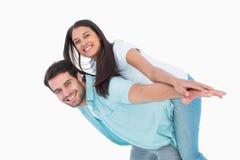 Happy casual man giving pretty girlfriend piggy back Stock Photos