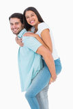Happy casual man giving pretty girlfriend piggy back Stock Image